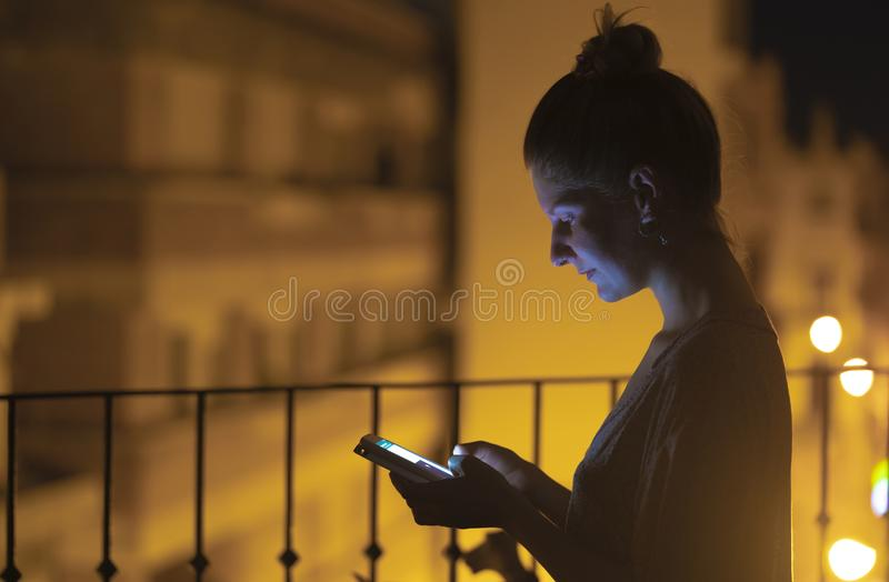 Mulher que olha seu smartphone na noite fotografia de stock royalty free