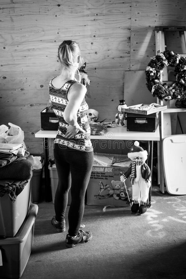 Mulher que olha sobre artigos da venda de garagem fotografia de stock royalty free