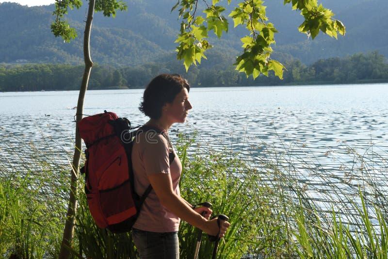 Mulher que olha um lago quando o sol se ajustar fotos de stock royalty free