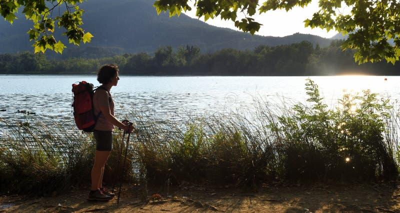 Mulher que olha um lago quando o sol se ajustar imagem de stock royalty free