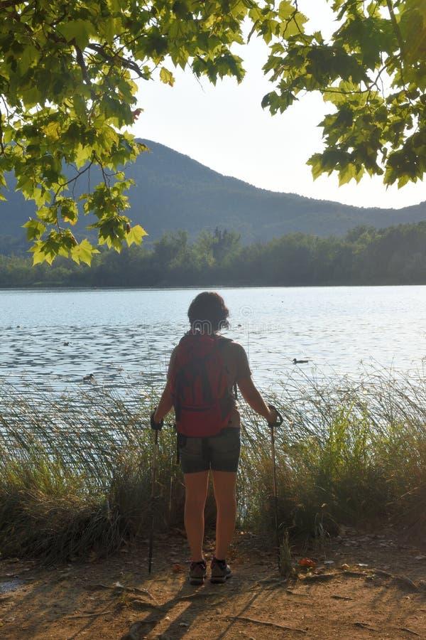 Mulher que olha um lago quando o sol se ajustar fotografia de stock royalty free