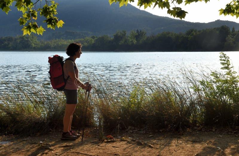 Mulher que olha um lago quando o sol se ajustar imagens de stock royalty free