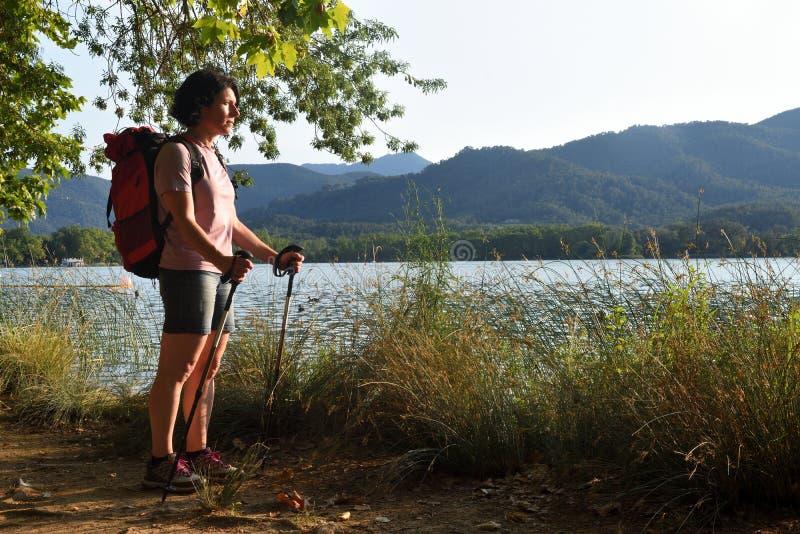 Mulher que olha um lago quando o sol se ajustar imagens de stock