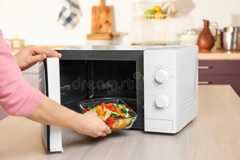 Mulher que põe a bacia com os vegetais no forno micro-ondas imagem de stock