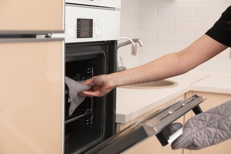 Mulher que põe a bandeja de cozimento no forno elétrico na cozinha fotos de stock