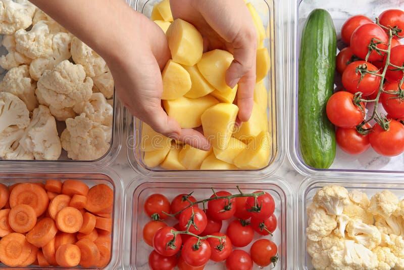 Mulher que p?e a batata cortada na caixa e nos recipientes com vegetais crus foto de stock royalty free
