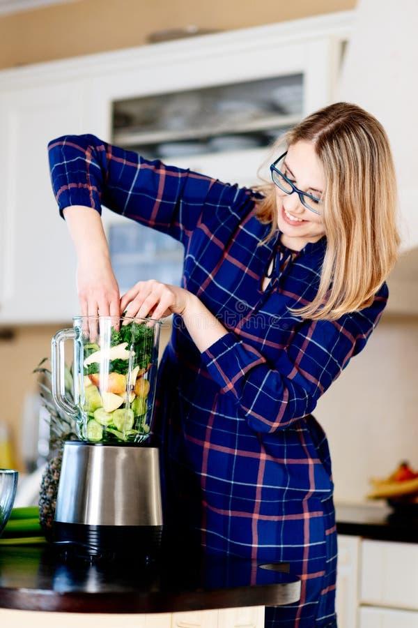 Mulher que põe frutas e legumes no misturador eletrical fotos de stock royalty free