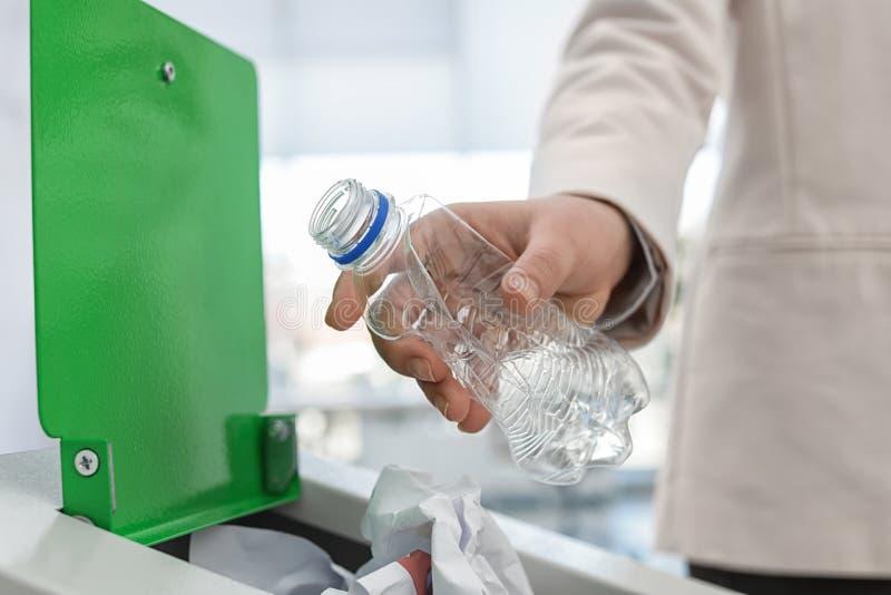 Mulher que põe a garrafa plástica usada no escaninho de lixo no escritório moderno Reciclagem de res?duos imagens de stock