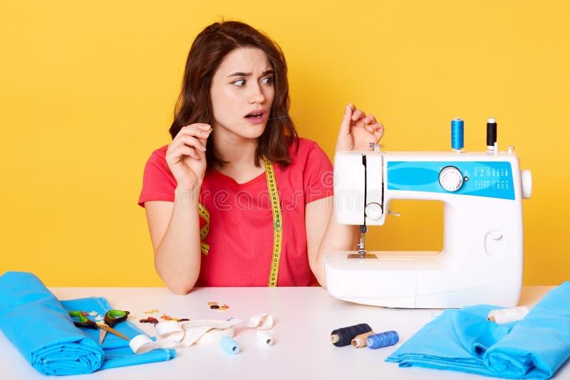 A mulher que põe a linha na máquina de costura, mantém as mãos acima ao costurar a roupa no trabalho autônomo, menina moreno vest fotos de stock royalty free
