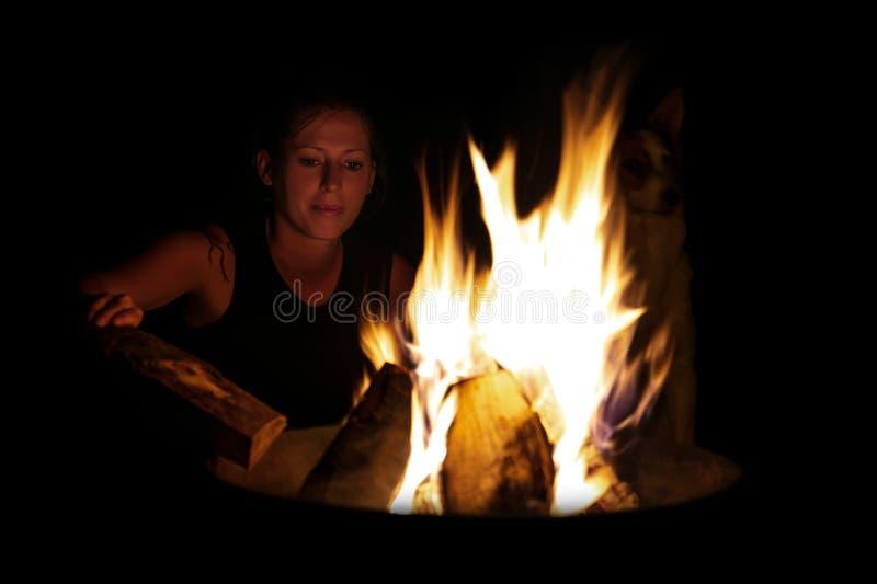 Mulher que põe mais madeira sobre o fogo, o acampamento e o assado no nig fotografia de stock