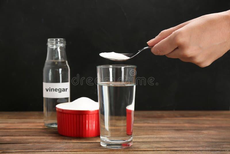 Mulher que põe o bicarbonato de sódio no vidro foto de stock