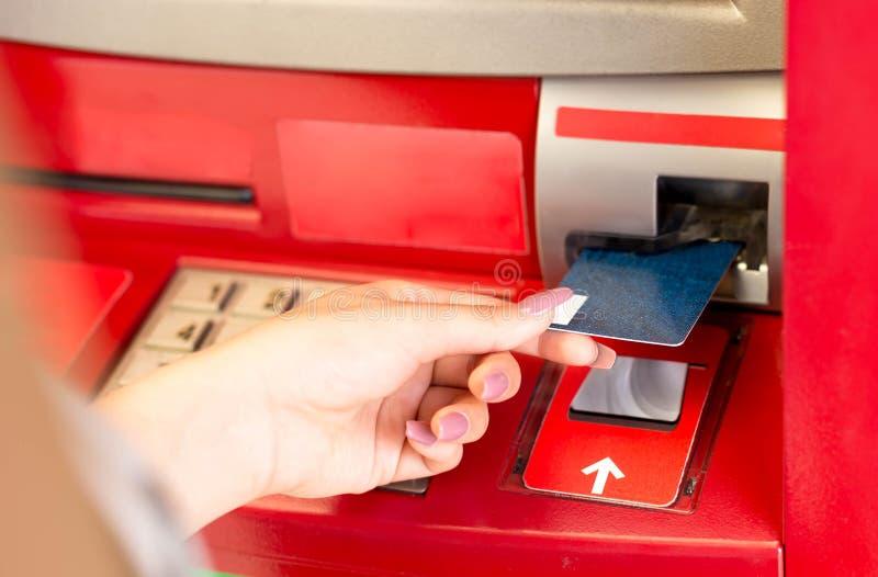 Mulher que põe o cartão na máquina de dinheiro do ATM imagem de stock