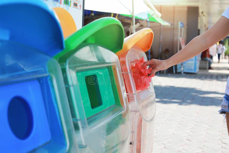 Mulher que põe o escaninho de reciclagem do saco de plástico no parque fotografia de stock
