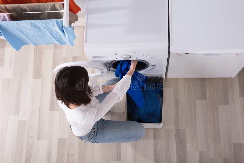 Mulher que põe o pano sujo na máquina de lavar imagens de stock