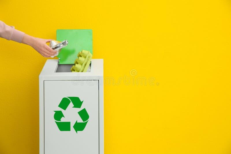 Mulher que p?e o recipiente usado da folha no escaninho de lixo sobre o fundo da cor Reciclando o conceito fotos de stock royalty free