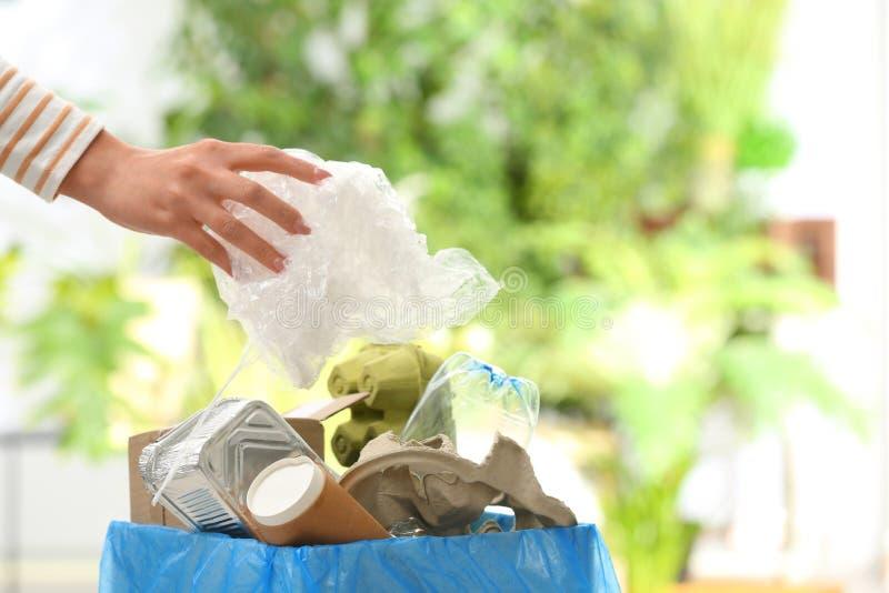 Mulher que põe o saco de plástico no escaninho de lixo sobre o fundo borrado, close up com espaço para o texto imagens de stock