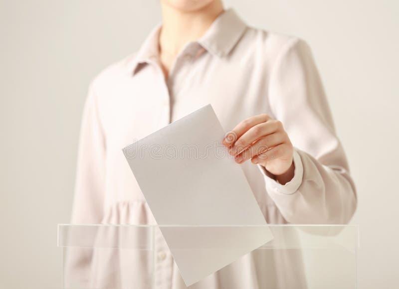 Mulher que põe o voto na urna de voto contra o fundo claro fotos de stock