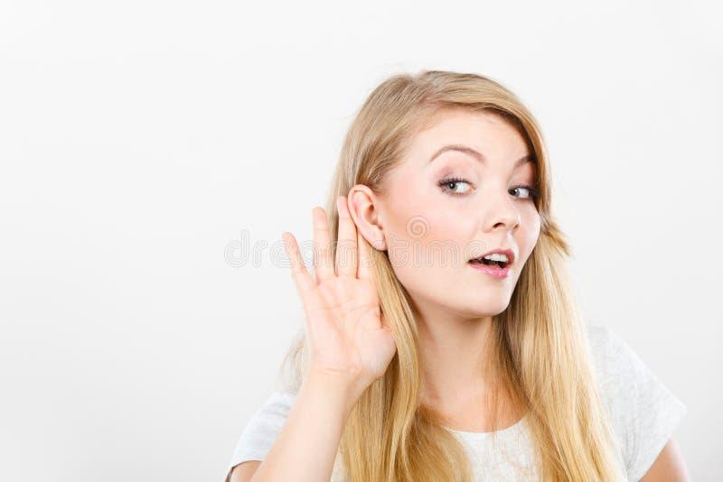 Mulher que põe a orelha da mão para ouvir-se melhor imagem de stock