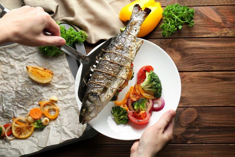 Mulher que põe peixes cozidos sobre a placa fotografia de stock