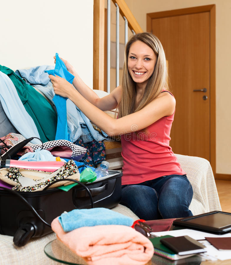Mulher que põe a roupa e os acessórios na mala de viagem fotografia de stock