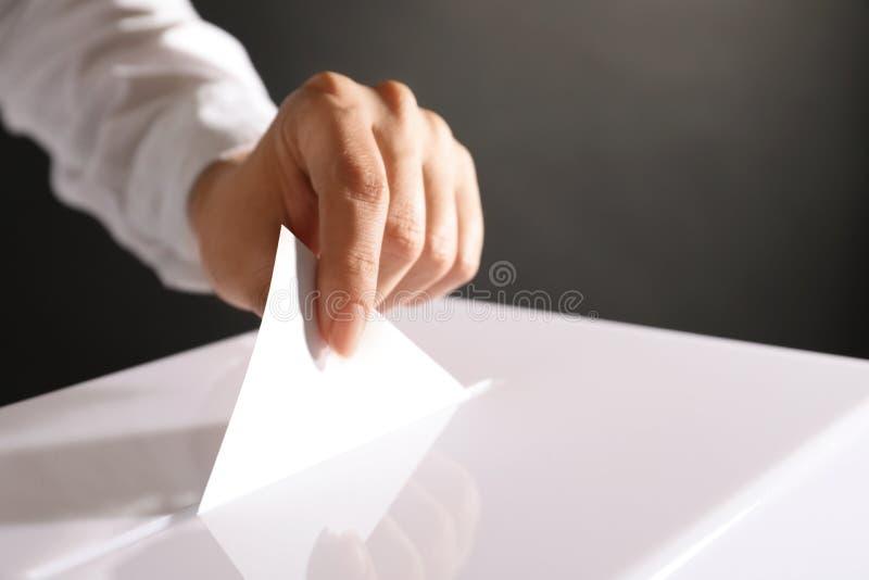Mulher que põe seu voto na urna de voto foto de stock royalty free