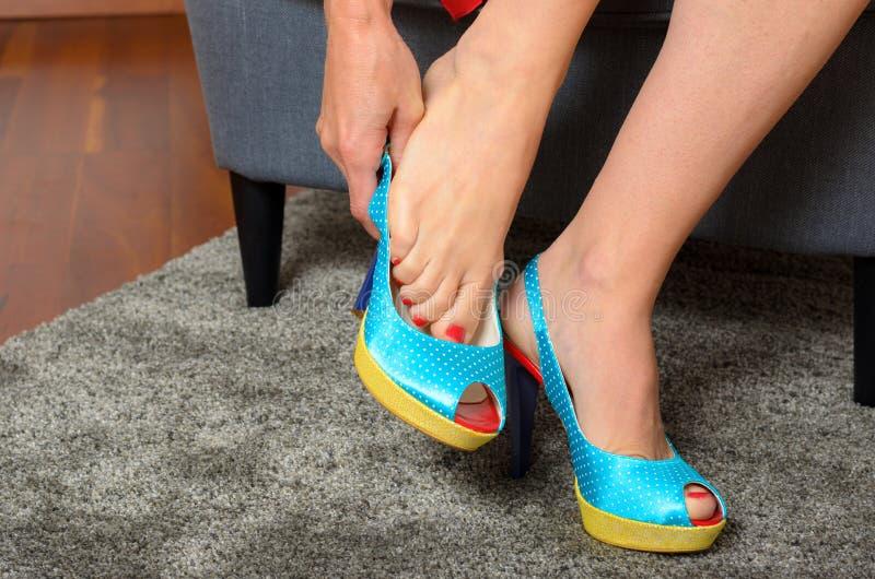 Mulher que põe sobre um par de sapatas azuis na moda fotos de stock royalty free