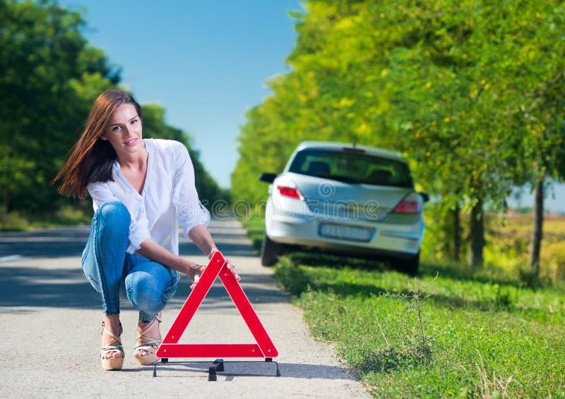 Mulher que põe um triângulo sobre uma estrada imagem de stock