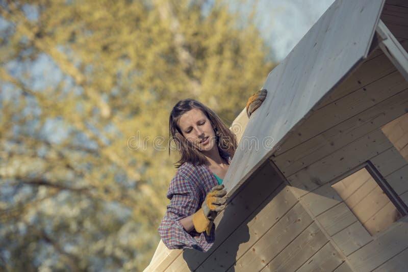 Mulher que põe uma prancha de madeira sobre o telhado da vertente do jardim fotografia de stock