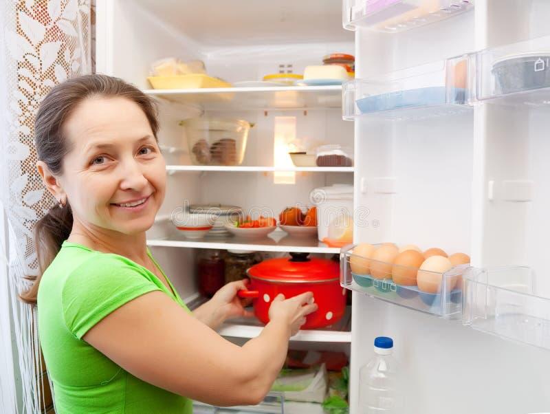 Mulher que põr a bandeja no refrigerador imagem de stock royalty free