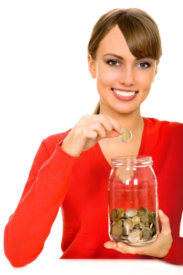 Mulher que põr o dinheiro no frasco fotografia de stock