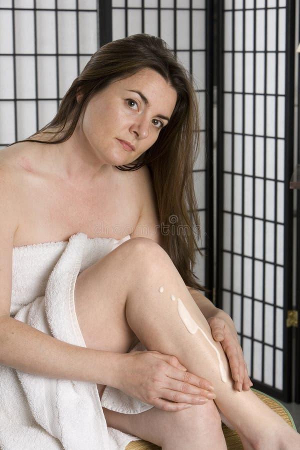 Mulher que põr sobre o creme de pele foto de stock