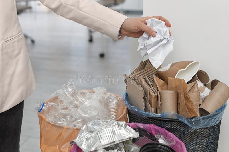 Mulher que p?e o papel amarrotado no escaninho de lixo no escrit?rio Reciclagem de res?duos imagem de stock