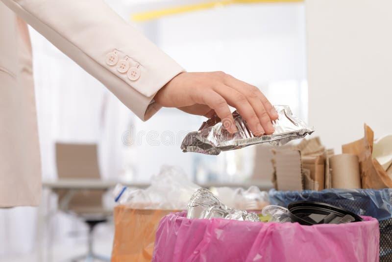 Mulher que p?e o recipiente usado da folha no escaninho de lixo no escrit?rio Reciclagem de res?duos imagens de stock