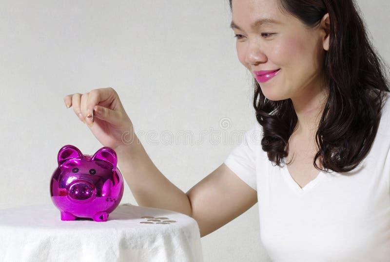 Mulher Que Pôr Uma Moeda Na Caixa De Dinheiro Foto de Stock