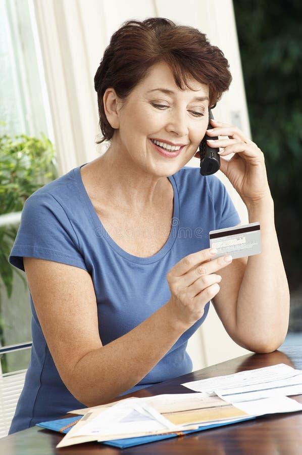 Mulher que paga o cartão de crédito usando o telefone celular imagem de stock