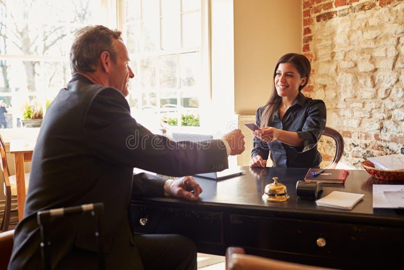 Mulher que passa a chave de sala a um convidado na mesa de registro do hotel fotos de stock