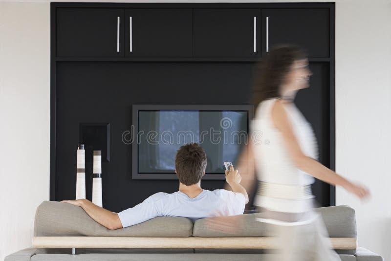 Mulher que passa pelo homem que usa o controlo a distância ao olhar a tevê fotos de stock