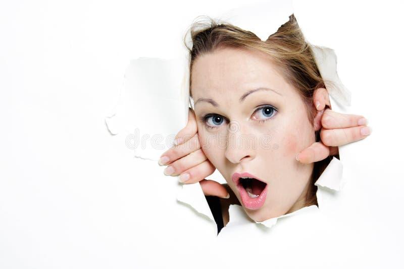 Mulher que peeping através do furo no papel imagem de stock