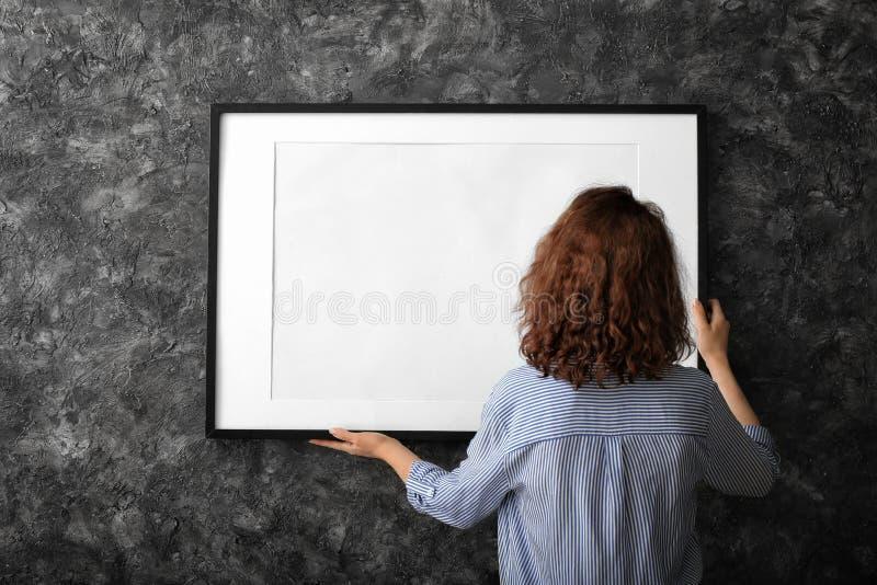 Mulher que pendura o quadro vazio da foto na parede escura fotos de stock royalty free