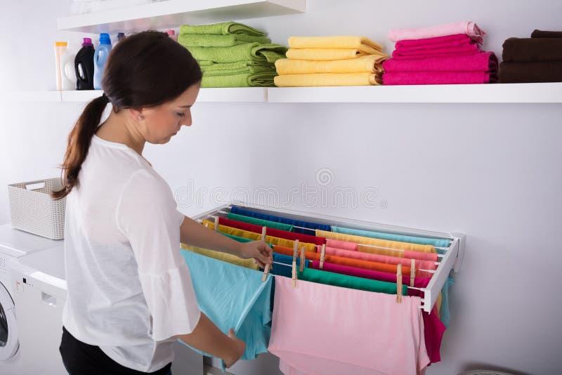Mulher que pendura a roupa molhada na lavandaria imagens de stock