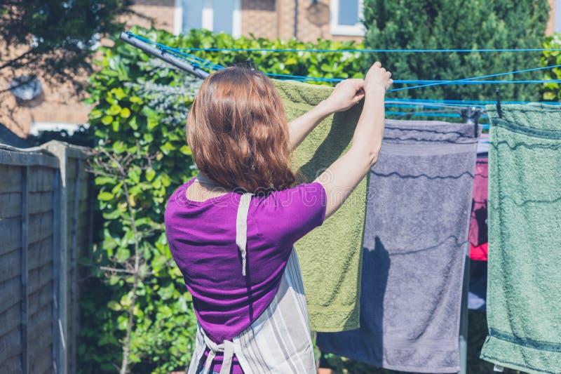 Mulher que pendura sua lavanderia no jardim fotos de stock