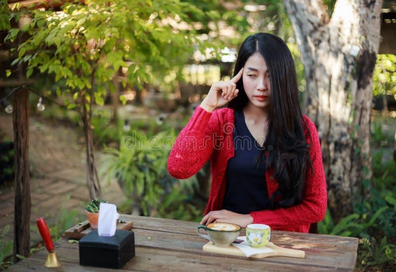 Mulher que pensa e que senta-se na tabela com café no jardim fotos de stock royalty free