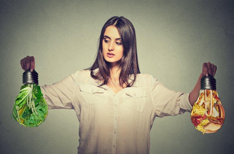 Mulher que pensa fazendo a comida lixo das escolhas da dieta ou vegetais verdes fotografia de stock royalty free