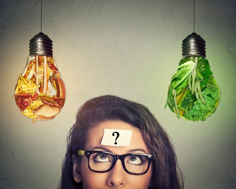 Mulher que pensa olhando a comida lixo e os vegetais dados forma como a ampola imagem de stock