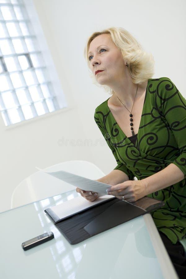 Mulher que pensa sobre a leitura foto de stock