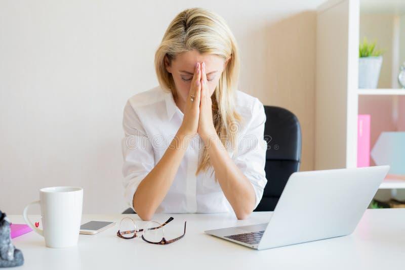 Mulher que pensa sobre problemas do trabalho no escritório foto de stock