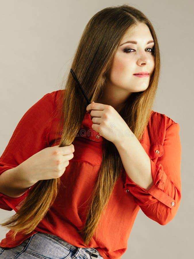 Mulher que penteia seu cabelo marrom imagens de stock