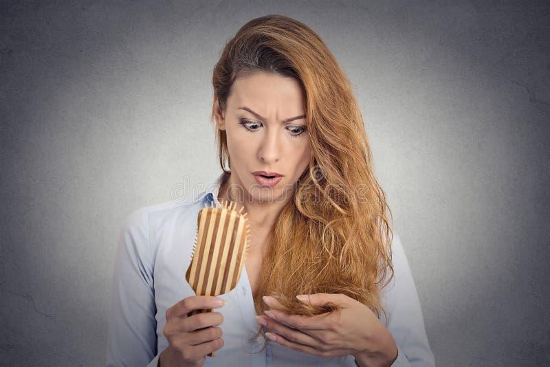 Mulher que penteia surpreendido é cabelo perdedor, entradas fotografia de stock royalty free