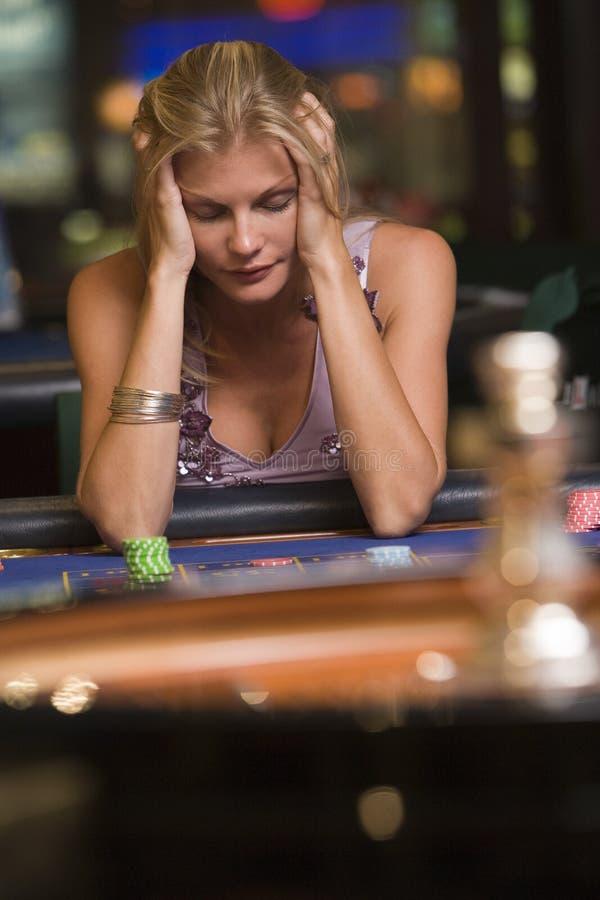 Mulher que perde na tabela da roleta imagens de stock