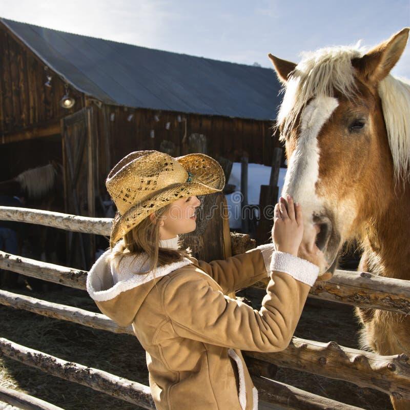 Mulher que petting o cavalo. fotos de stock